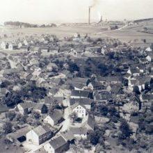 Historische Luftaufnahme des Ortes mit dem Grubenschlot von Schacht III